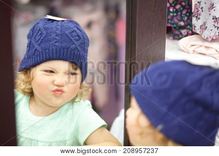 Cute Little Girl Choosing Clothes In The Shop