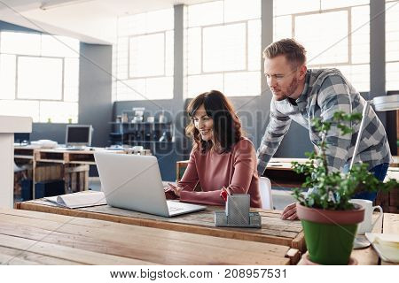 Two casually dressed young business colleagues using a laptop and talking together while standing at a table in a modern office