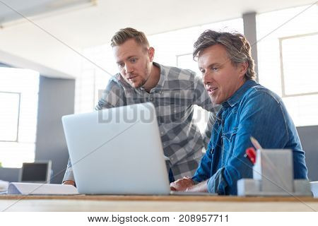 Two casually dressed businessmen talking and using a laptop while working together at a desk in a bright modern office