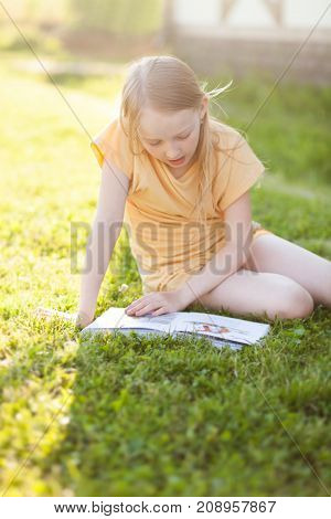 Blonde teenager girl doing her summer homework in the backyard learning and reading. Beautiful natural light.
