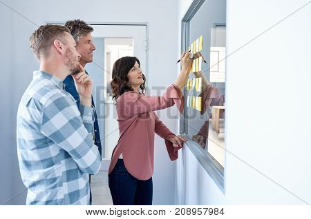 Group of casually dressed work colleagues brainstorming together on a glass window with sticky notes while standing in a modern office