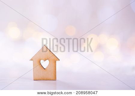 Wooden House With Hole In The Form Of Heart On Light Bokeh Background