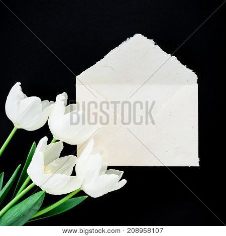 Paper envelop with white flowers. Flat lay, top view, isolated on black background