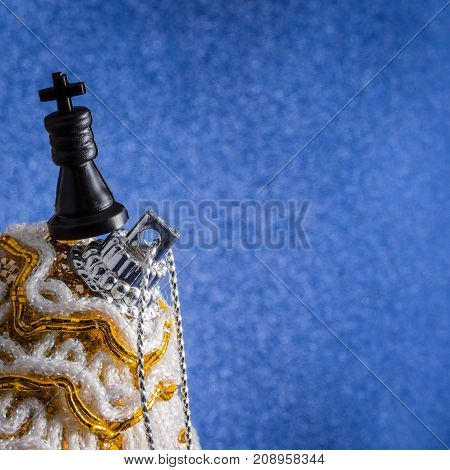 black chess king at the top of a Christmas toy on a blue background