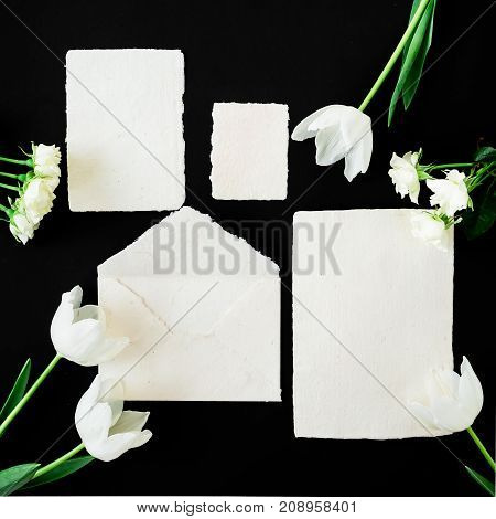 Paper envelop with white card and tulip flowers. Flat lay, top view, isolated on black background