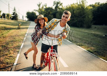 Love couple fun in summer park, vintage bicycle