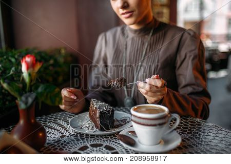 Woman eating delicious chocolate cake in cafe