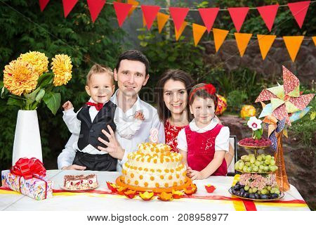 Family Of Four People Father Mom Son And Daughter Celebrates Daughter's Birthday Three Years Sitting