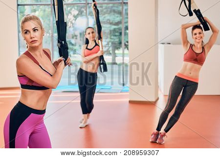 Women with fitness straps in the gym Concept workout healthy lifestyle sport. focus is on one girl