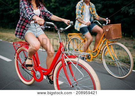 Male and female persons riding on retro bikes
