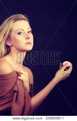 Smell elegance concept. Beautiful elegant blonde woman with necklace holding and applying perfume after shower studio shot on dark background