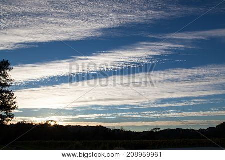 A blue sky in late afternoon with the setting sun highlighting striped clouds and framed by landscape and trees.