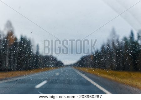 Rain drops on windscreen and blurred autumn forest road on background.