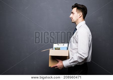 Dismissed Businessman Carrying Box. Isolated On Gray