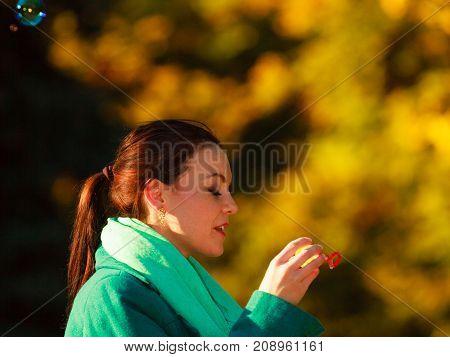 Woman Walking In Park Making Soap Bubble