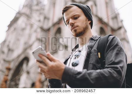One more close up of a serious traveller that enjoyes his trip. The gus is standing near gothic church in some city and looking to the phone's screen. He is probably searching for his friend's phone number. Cut view