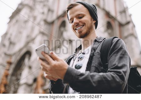 Another close up of a young traveller standing at the cathedral and looking to the phone's screen. He is smiling because he has finally found his friend's phone number. Cut view