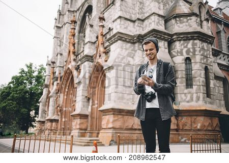 Smart and good-looking yourist is standing at the church building and looking to his phone. He is holding it in his hands and waiting for his friend coming today.