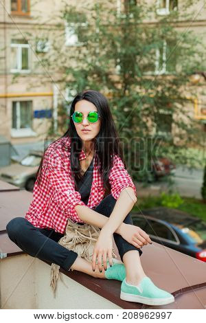 gorgeous young girl in spectacles sitting on roof building, cool woman in pink jacket and black pants with bag resting outdoor