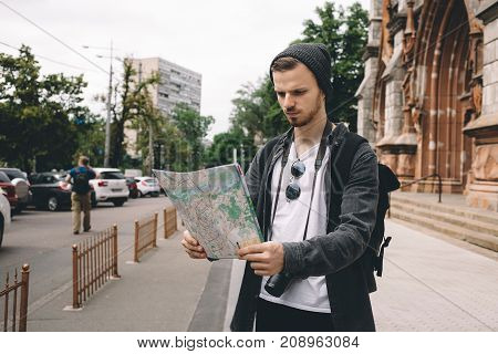 A picture of tourist standing besides cathedral building and looking to the map. Seems like this guy has been lost in the big city and now he is trying to find his current location.
