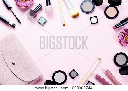 Make up products frame on a pastel pink background, copy space, top view