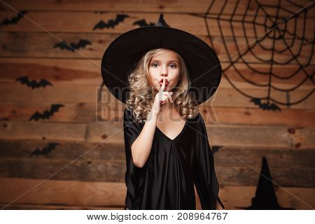 Halloween Witch concept - closeup shot of little caucasian witch child holding index finger at lips asking to keep silence.