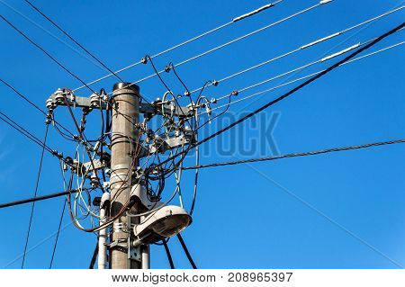 Utility pole or power pole. Column with electric disconnect power. Blue clear sky. Three-phase power line connection