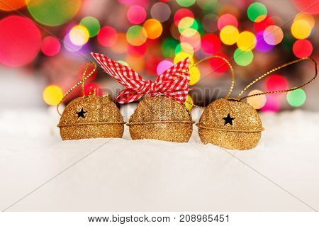 Greeting Christmas Card with Gold Jingle Bells on Colorful Bokeh Background