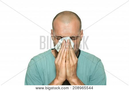 Cold flu. Young man sick from common cold flu blowing his nose with paper tissue isolated on white background