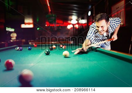 Hansome man playing pool in bar alone aiming