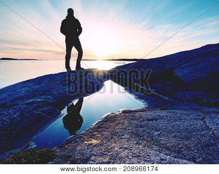 Tall Hiker In Dark Sportswear With Backpack Stands On Cliff Above Sea. Man Enjoy Amazing Sunset
