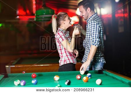 Happy couple drinking beer and playing snooker on date