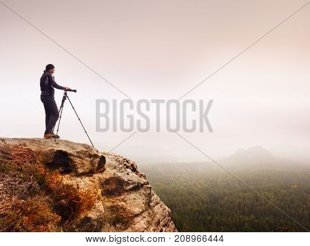 Professional Photographer Takes Photos Of Misty Landscape With Mirror Camera And Tripod.