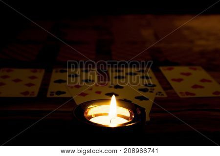 Mystic Halloween fortune telling concept. Burning candle with playing cards in darkness on wooden background