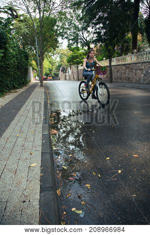 Young attractive woman riding a bicycle on wet road after rain. Sunny morning bike walk on vacation.