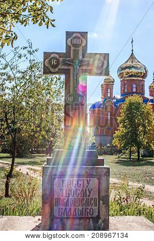 Pokrov Ukraine - October 12 2017: The Christian cross in the sun's rays and The orthodox Church of THE HOLY APOSTLES AND THE GOSPEL JOHN OF BOGHOSLOV
