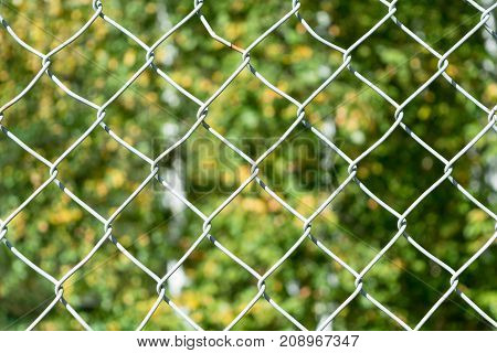 In the foreground grille mesh netting. In the background a blurry image of the leaves of trees. The fence prevents passage in a closed area or private property. The restriction of freedom of movement.