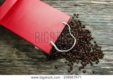 Coffee beans were scattered from the red packing on a wooden table. View from above