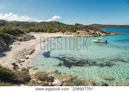Boat Moored In A Small Cove With Sandy Beach In Corsica