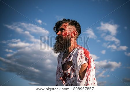 Halloween evil and horror. Injury hurt pain. Man with red blood splatters on bearded face. Zombie hipster in torn tshirt with bloodstains on blue sky. War soldier or victim concept.