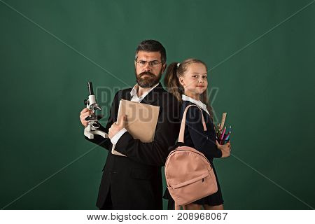 Man and girl with bag wearing school uniform. Kid and tutor hold microscope book and stationery. Teacher and schoolgirl with proud faces on dark green background. Education and back to school concept