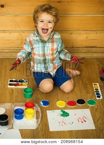 Arts and crafts. Child shouting with colored hands gouache paints and drawings. Imagination creativity and freedom concept. Boy painter painting on wooden floor. Happy kid learning and playing.