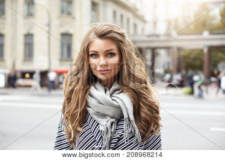 Headshot of charming Caucasian young woman with light-brown wavy hair dressed in stripped coat and big grey scarf staring at camera with lazy smile standing on European city background