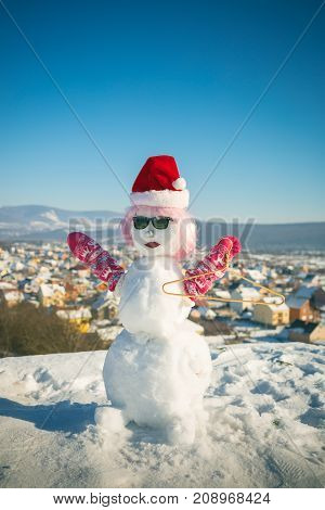 Christmas and xmas decoration. Snowman in pink wig mittens hat and glasses. New year snowman from white snow with hanger. Santa at happy holiday and celebration. Winter fashion and party.