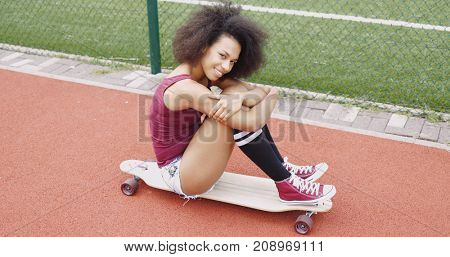 Beautiful young model in stylish clothing sitting on wooden longboard embracing knees and looking at camera smilingly.