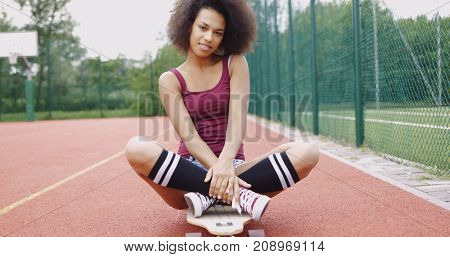 Charming ethnic model in knee socks and shorts posing on longboard with legs crossed and looking at camera flirting.