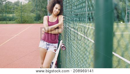Pretty young ethnic woman in casual clothing leaning on fence with longboard near and looking at camera on background of sports ground for basketball.