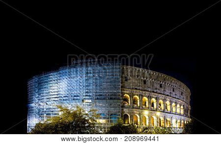Coliseum with scaffolding under restoration at night Rome Italy. Roman amphitheatre with light illumination on dark sky. Renovation repairing retouching concept. Landmarks and architecture.