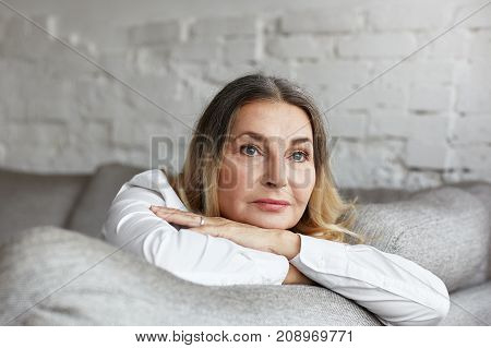 Picture of attractive middle aged Caucasian woman with long straight hair resting on grey comfortable sofa having sad unhappy expression feeling bored or lonely. People lifestyle and age concept