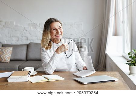 Experienced mature female chief editor holding glasses in one hand and book in other laughing at sarcastic style of narration while reading novel of popular author. Writing and publishing concept
